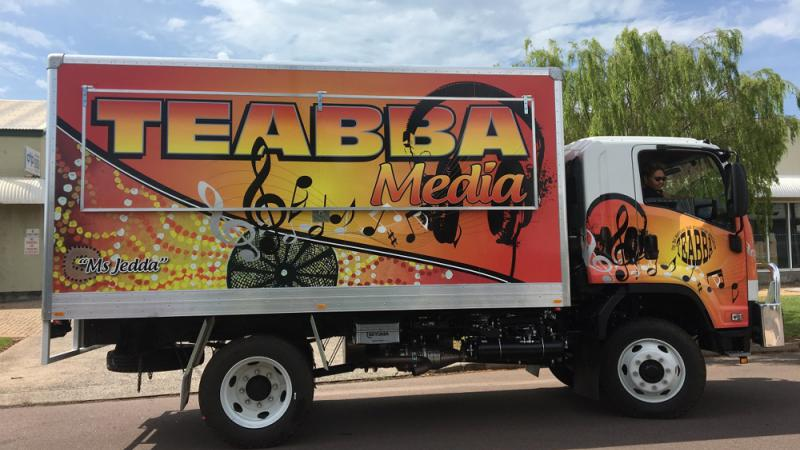A large truck belonging to TEABBA Media is covered with Indigenous dot patterns.