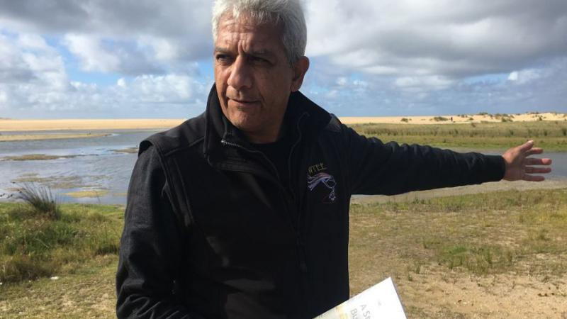 Aboriginal man in dark jacket holds a book in his right hand and points with his left. In the background is grass, water, sand and sky.