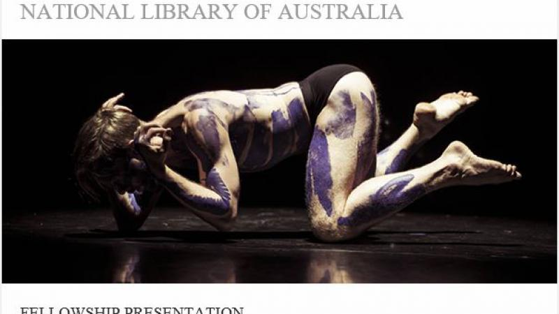 Main painted with purple Indigenous designs on hands and knees on a smooth black floor. Above and below him are the words National Library of Australia and Fellowship Presentation.