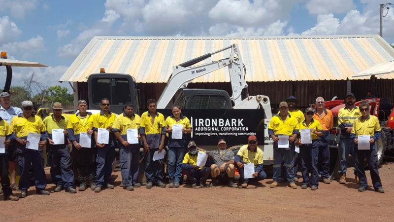 A group of men and women holding certificates while standing in front of heavy machinery and a shed.