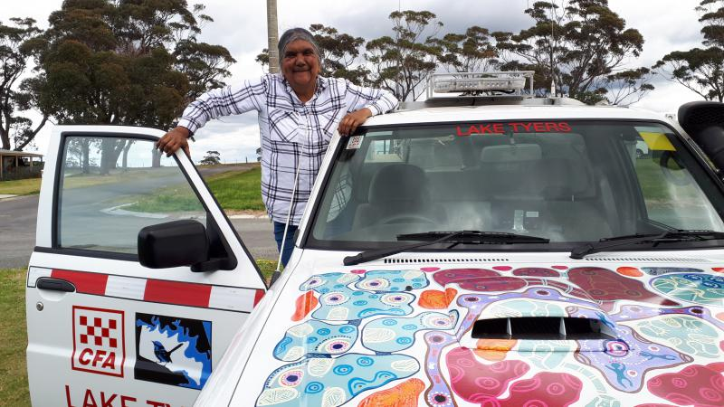 A car with a brightly painted front with the words Lake Tyers CFA written on the vehicle. A woman is standing in the door of the vehicle with the door open and smiling wearing a white and black striped shirt.