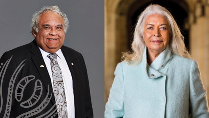 Elderly Indigenous man in suit and tie stands next to elderly Indigenous woman in blue coat.