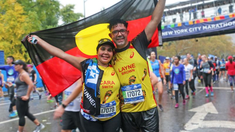 An Aboriginal woman and man stand on a street holding the Aboriginal flag. Behind are many people dressed in running wear crossing a finish line, above which hangs a banner on an overhead walkway.