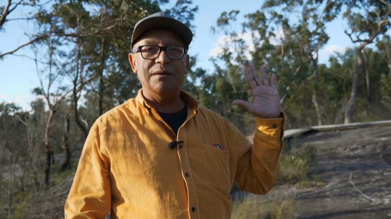 Elderly man in yellow shirt and peaked cap stands with left hand raised. In the background are trees and bare ground.