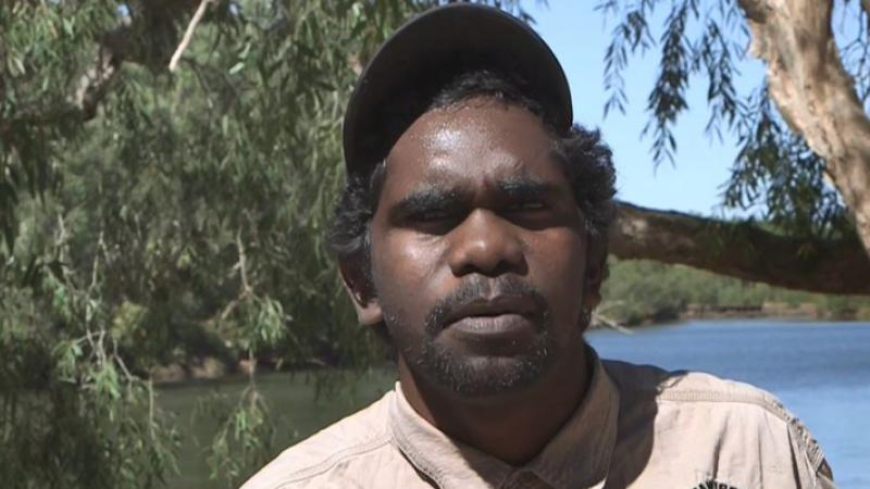 Aboriginal young man dressed in ranger uniform in foreground with river and trees in the background.