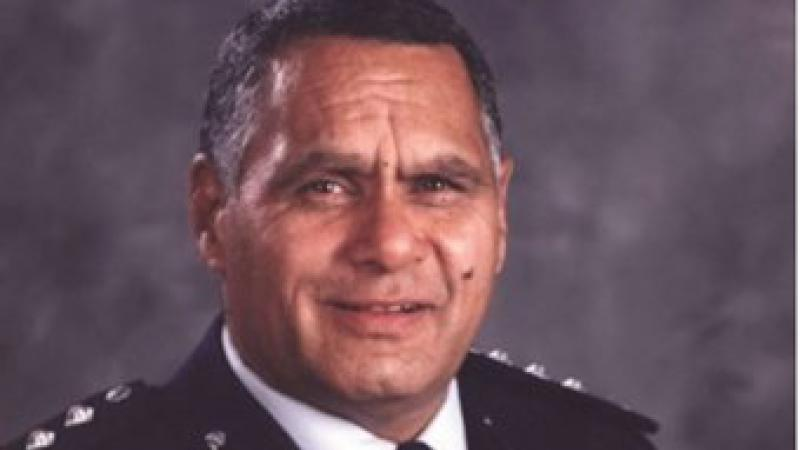 Head and shoulders shot of Indigenous man dressed in police officer's uniform.