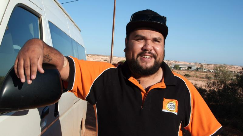 Indigenous man leaning up against a white van with buildings in the background.