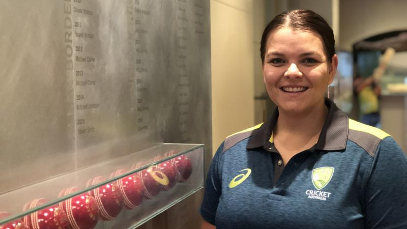 Aboriginal woman in dark blue shirt stands next to a glass display cabinet featuring red cricket balls.