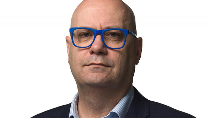 AIATSIS CEO, Craig Ritchie, posing in front of a white background with blue framed glasses, light blue shirt and navy blue blazer.