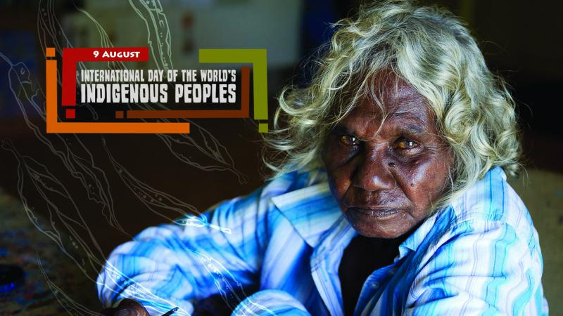 White haired Aboriginal woman wearing blue and white collared shirt sits on a floor. To her left is a graphic of leaves and the following words: 9 August International Day of the World's Indigenous Peoples.