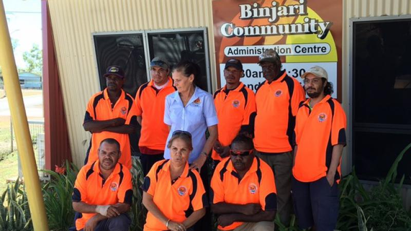 Two rows of nine Indigenous persons dressed in orange shirts (one in blue) stand and kneel in front of a yellow building with a sign on the wall which says, Binjari Community Administration Centre.