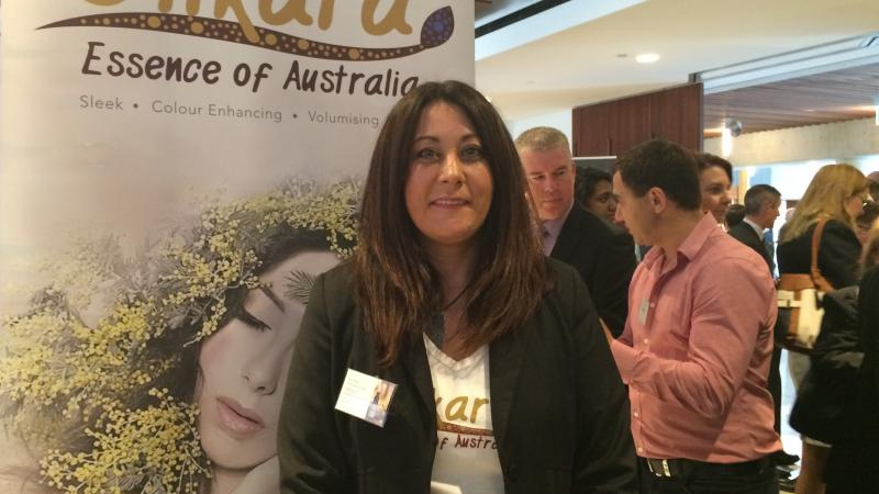 A woman, Julie Okley, stands in front of a poster displaying the words Dilkara, Essence of Australia. There are other people in the background.