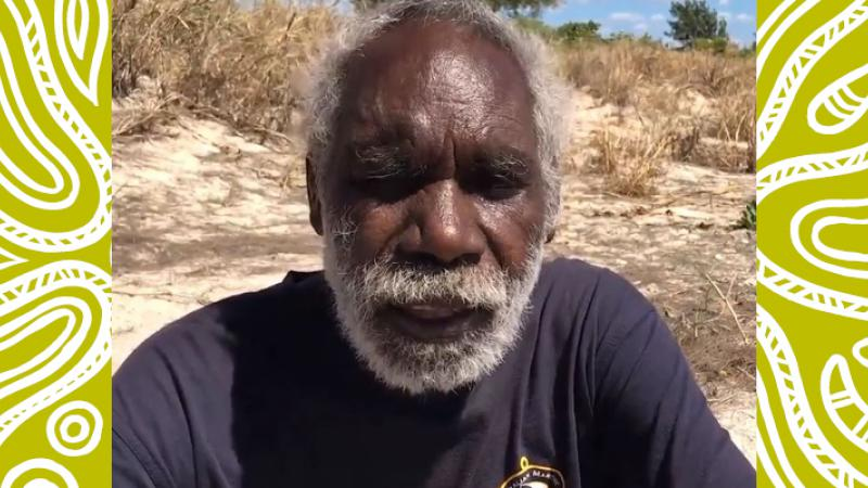 "Image of an Aboriginal fisherman sitting on the ground in a dark blue shirt. An orange rectangle with the words ""Don Wilton"" is in the right hand corner."