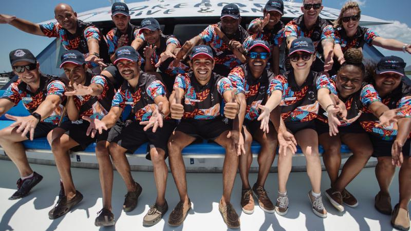 Group of Indigenous adults sitting on the front of a boat and dressed in uniforms displaying an Indigenous design.