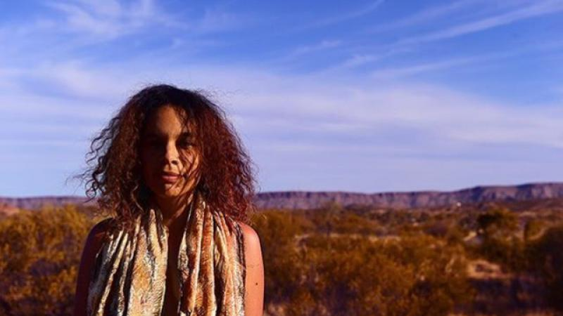 Aboriginal woman with long wavy hair and wearing scarfs around her neck stands in open bushland with a range of hills in the background.