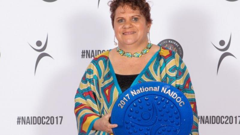 An Aboriginal woman in a colourful top holds a large blue plate.