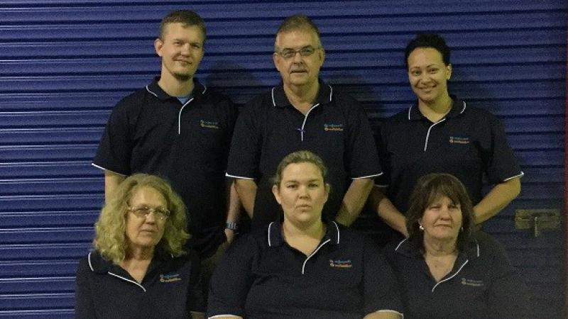 Two rows of people dressed in blue polo neck shirts in front of a blue roller door; three standing in the back row and three are sitting in the front.