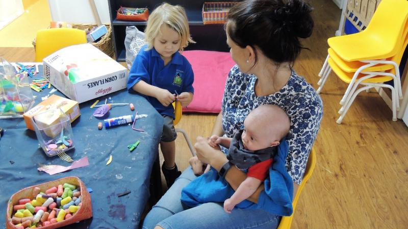 Woman in blue and white blouse sits at small table with craft materials. She holds a baby while looking at a young child in blue shirt working with craft material.