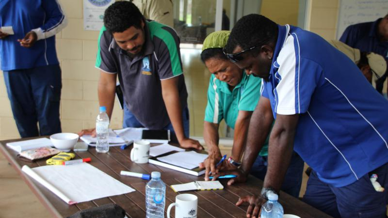 Three Torres Strait Islanders are standing at a desk looking at a note book. The woman in the middle is explaining something to the two men around her. There are other people in the background.