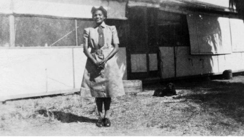 A woman wearing a uniform and hat, stands on grass in front of a building.