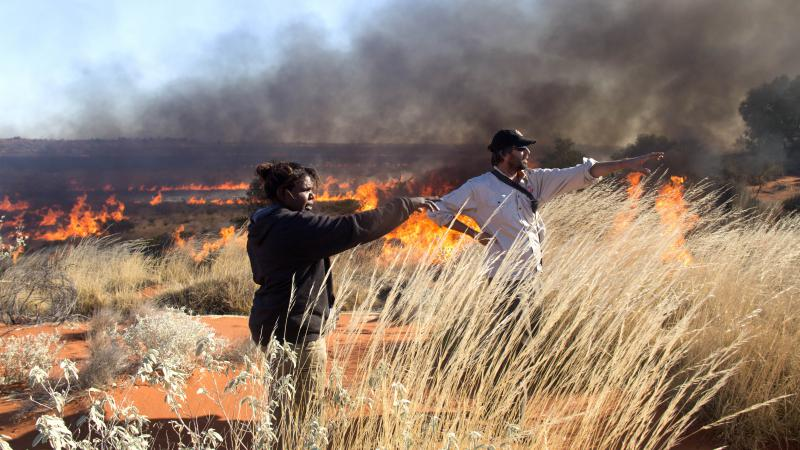 Female ranger and male ranger standing in desert setting with burning grass in the background.