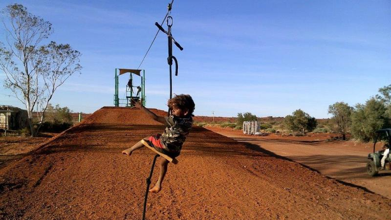 Aboriginal child on a cable suspended over brown soil. In the background is bare soil and some trees.