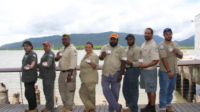Line of Indigenous men and women dressed in ranger uniforms display their individual ranger accreditation. In the background is a wharf, a bay and a hill.
