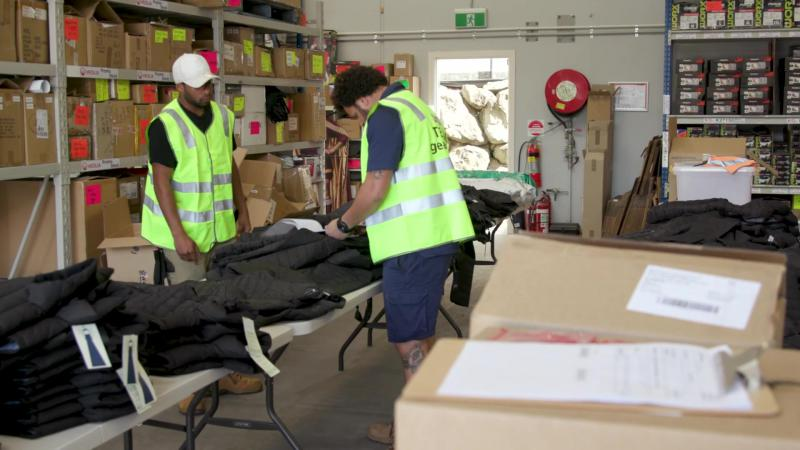 Two men wearing high-visibility vests and blue shorts working in a warehouse filled with boxes. In front of the two men are tables piled with jackets and work clothing.