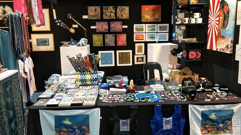 Souvenirs and gifts are displayed on a black wall and a black table. Included are items like necklaces, cards, shirts and paintings.