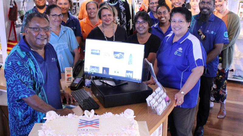 A group of adults in various forms of dress stand behind a large cake. They are in a room with a board floor and on the wall at the back are items for purchase. At the front and behind the cake is a computer.
