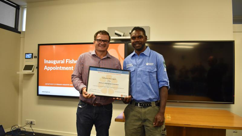 Two men stand side by side and hold between them a large framed certificate. The man on the left wears a checked shirt and dark trousers. The man at right wears a blue shirt and green trousers. They stand in a room with two large TV screens in the back.