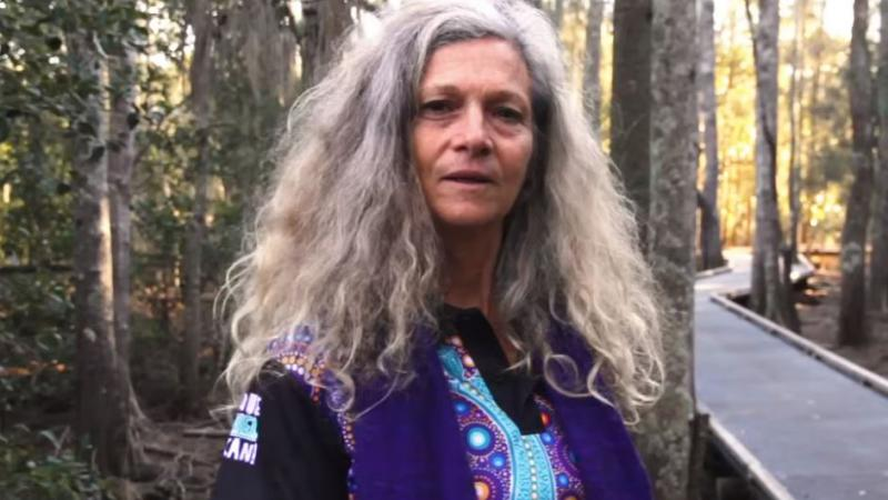 A woman with long greying hair and wearing a purple and blue shirt with Aboriginal designs stands next to a walkway in a forest.