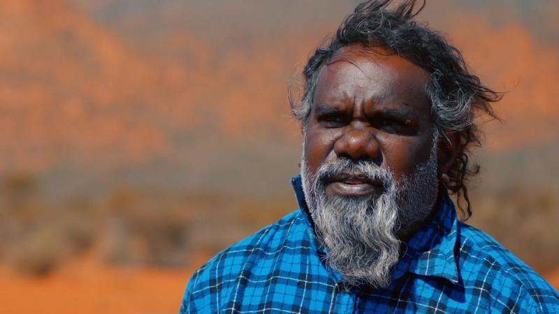 Head and shoulders shot of Aboriginal man with greying beard and wearing a blue checked shirt. In the background is an arid and ochre coloured landscape.