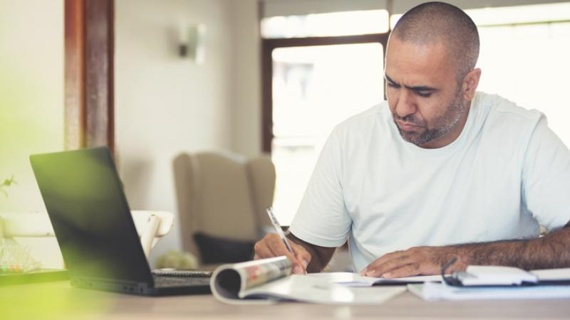 A man in white t-shirt and shaven head sits at a desk writing. In front of him is a laptop, a magazine, papers and booklets. In the background is a wall and windows.