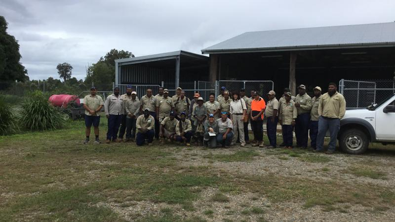 Group of Indigenous people dressed in ranger clothing, stand or squat in front of a shed and white vehicle on grass and gravel covered ground.