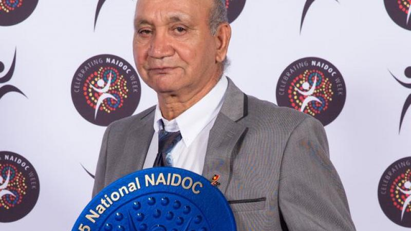Indigenous man dressed in grey suit holding blue plate displaying the text 2015 National NAIDOC