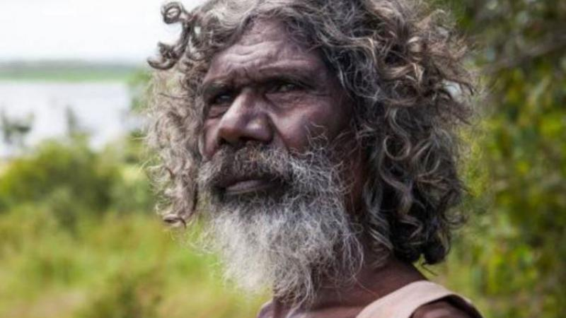 Bearded Aboriginal man with greying hair and wearing a singlet stands in front of green vegetation.