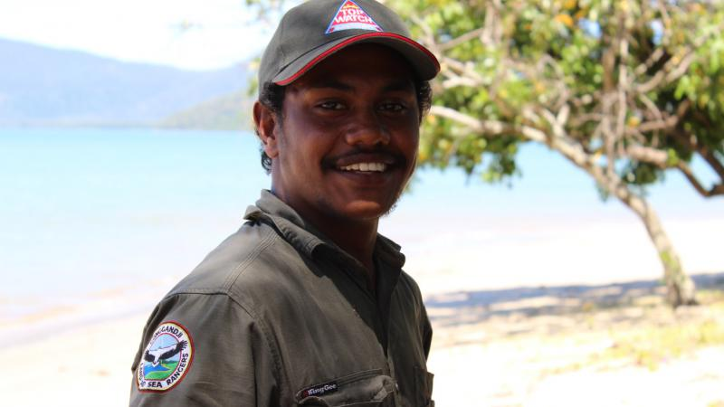 Indigenous young man dressed in ranger clothing standing near tree with body of water and hills in the background.