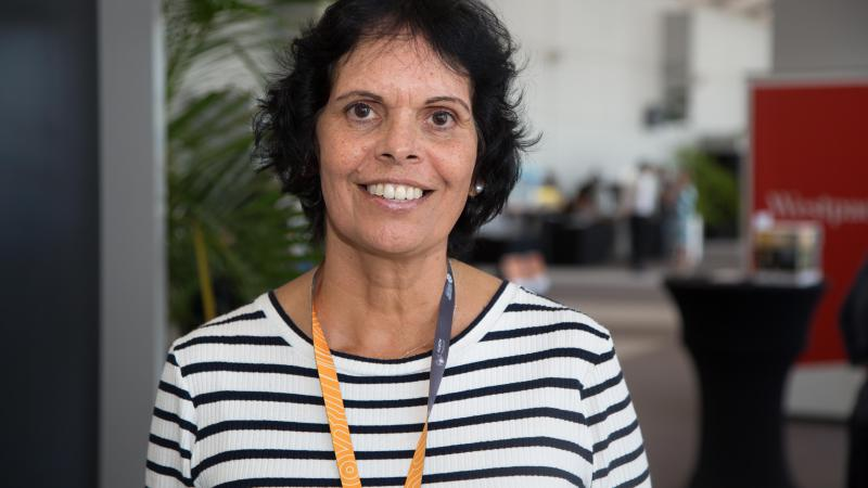 Indigenous woman with dark hair and white shirt with thin navy stripes smiling at Darwin Indigenous Trade Fair.