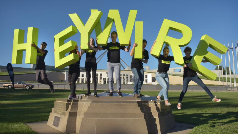 A group of 7 young people are standing on a cement block, in the background is Parliament House. Each person is holding up a giant green letter that spells HEYWIRE