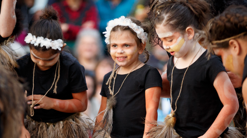 Young Indigenous girls with face paint and wearing black tops and grass skirts stand next to each other. In the background are more people.