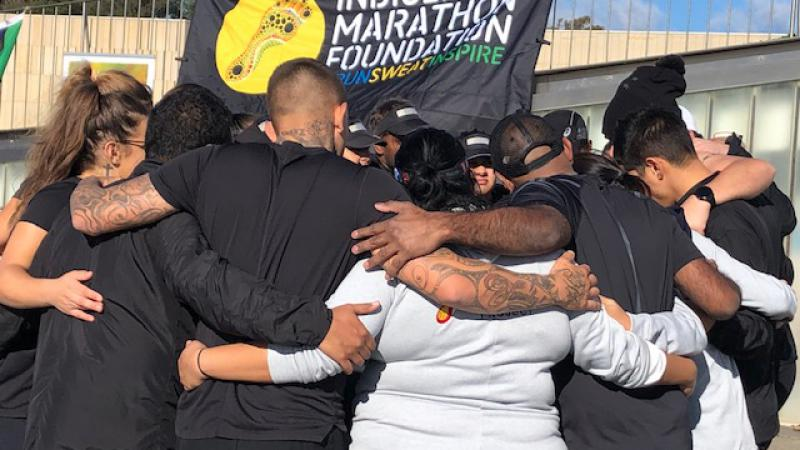 A group of men and women stand in a huddle with their arms wrapped around each other. Behind them is blue sky and a sign moving in the wind. The sign shows the words: Indigenous Marathon Foundation #Run Sweat Inspire