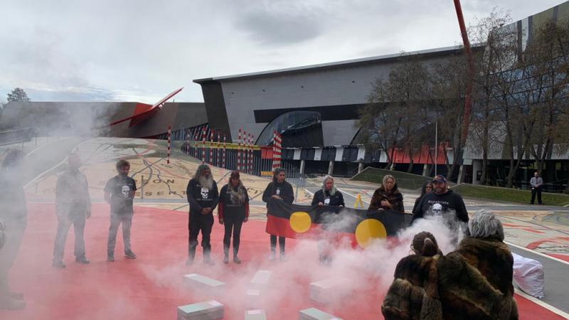Group of Aboriginal people, some dressed in traditional wear, stand around boxes on a red paved area with smoke rising from a small fire. In the background is a large building and sculpture.