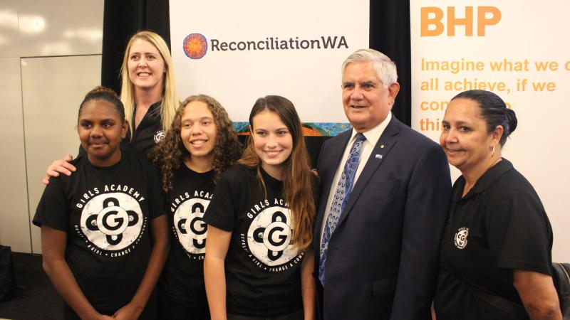 3 young women in black and white t-shirts stand in front of a woman and next to an elderly man in a suit who is next to another woman in a black shirt. Behind them are signs which say Reconciliation WA and another says BHP Imagine what we can all achieve