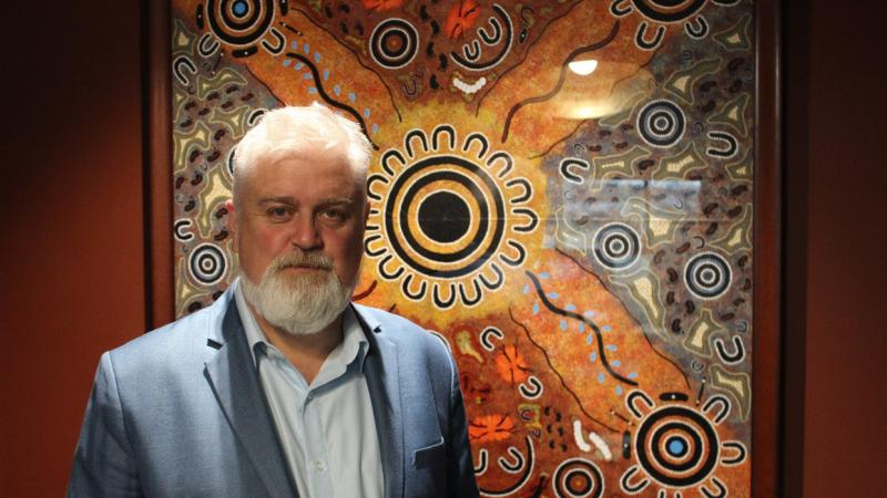 Aboriginal man with white beard and hair, dressed in blue suit and shirt stands in front of artwork of Indigenous design featuring circles, horseshoe shapes and squiggly lines.
