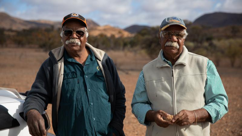 Two senior Aboriginal men stand next to a white car with trees and hills in the background.