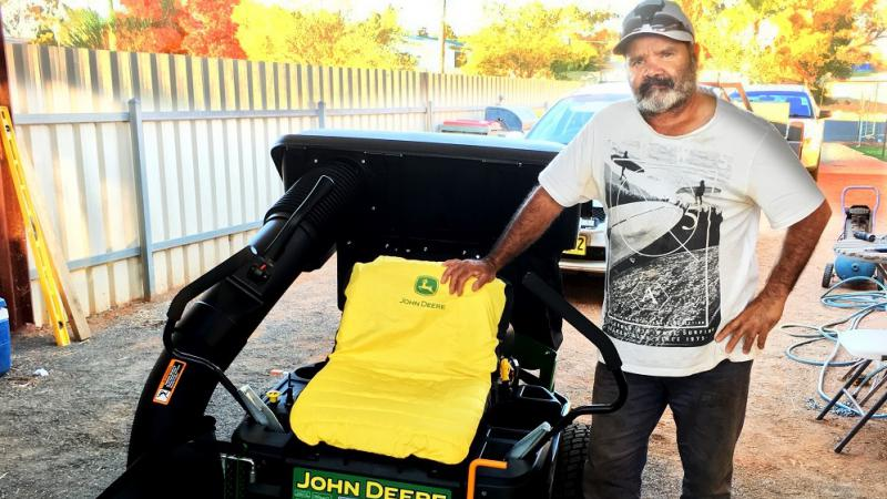 Aboriginal man in white and black t-shirt stands next to a black, yellow and green coloured ride-on lawn mower. In the background is a car, a fence and other equipment.
