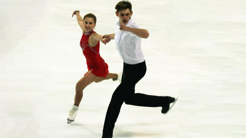 Young woman in red dress holds hands and skates with Indigenous young man in white shirt and black pants.