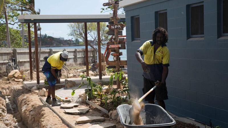 Two Indigenous men working on a landscaping project