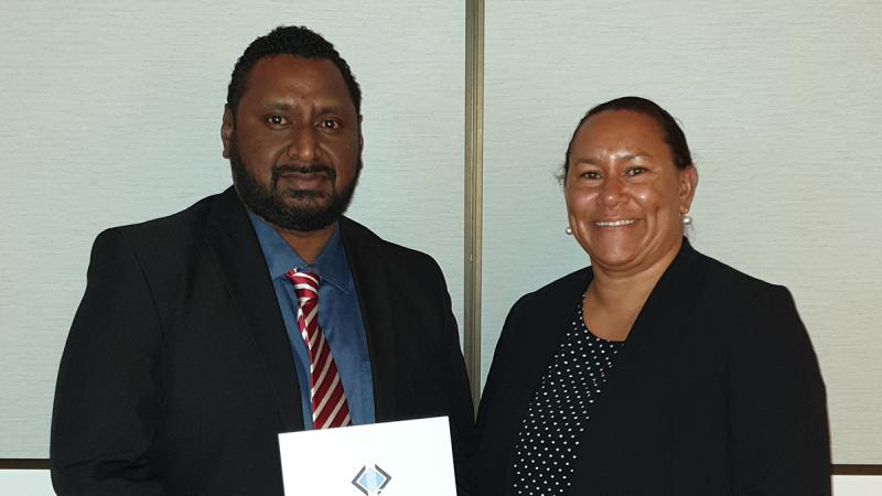 Indigenous man in jacket and tie holds a certificate. Next to him is an Indigenous woman in black jacket.